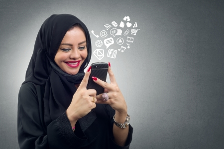 Arabian lady wearing hijab using her mobile with virtual apps icons