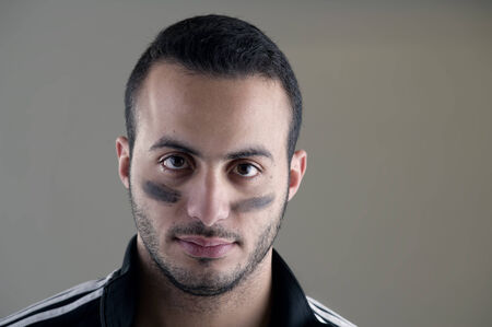 face paint: Portrait of a football player looking at the camera