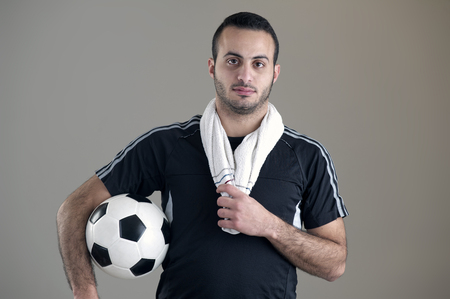 Portrait of a football player holding his ball isolated on grey background