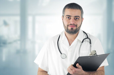 Doctor Standing At The Hospital holding a Clipboard photo