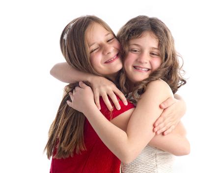 niñas gemelas: Dos hermosas hermanas abrazos aislados en blanco