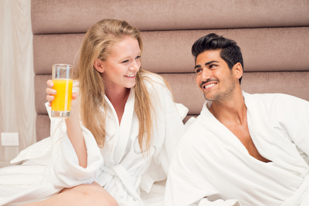 bath robes: Young happy couple having breakfast in luxury hotel room.