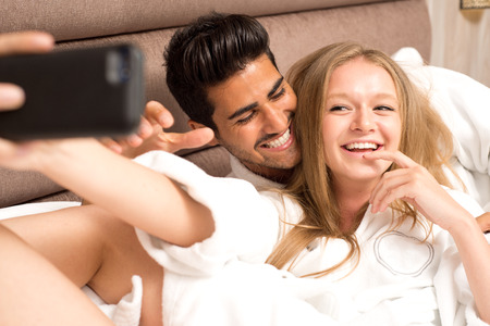 Couple in bed taking a selfie and having fun Imagens