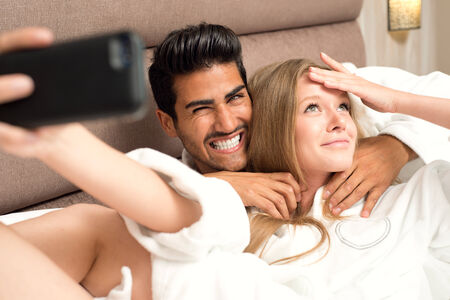 romantic room: Couple in bed taking a selfie and having fun Stock Photo