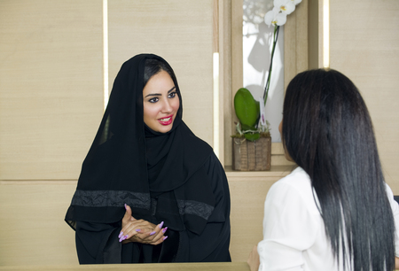 Arabian Receptionist helping a customer on the front desk Stock Photo