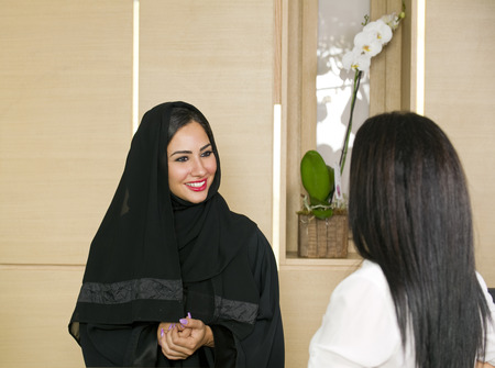 Arabian Receptionist helping a customer on the front desk Imagens