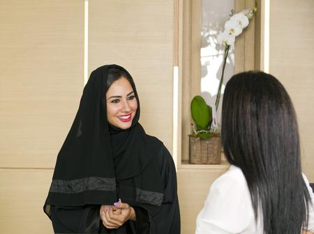 Arabian Receptionist helping a customer on the front desk Standard-Bild