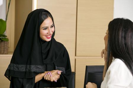 KSA: Arabian Receptionist helping a customer on the front desk Stock Photo