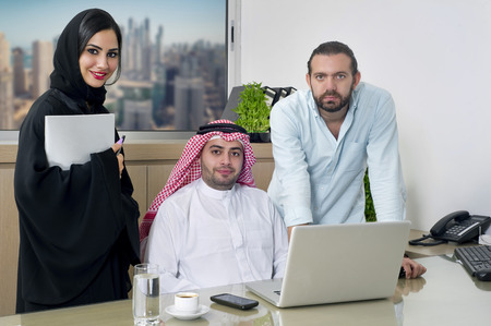 uae: Multiracial Business Meeting in office , arabian businessman & arabian Secretary wearing hijab & a Foreigner meeting in office