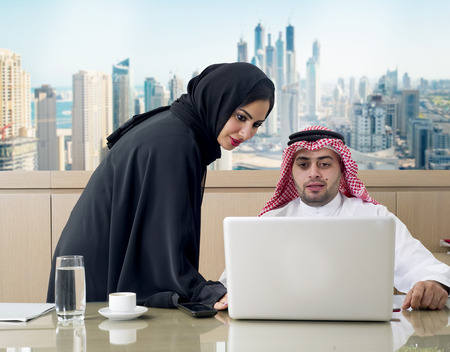 Business Meeting in office , arabian businessman & arabian Secretary wearing hijab working on laptop photo