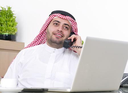 hombre arabe: El hombre de negocios �rabe usa la computadora port�til y hablando por tel�fono Foto de archivo