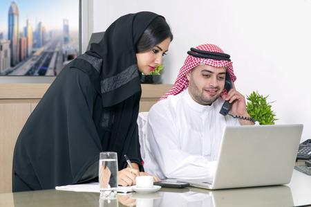 hijab: Business Meeting in office , arabian businessman & arabian Secretary wearing hijab working on laptop