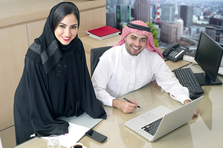 successful business woman: Business Meeting in office , arabian businessman & arabian Secretary wearing hijab working on laptop