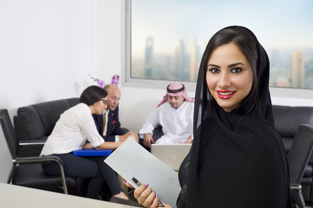 saudi: Arabian Businesswoman with Employees meeting in the background