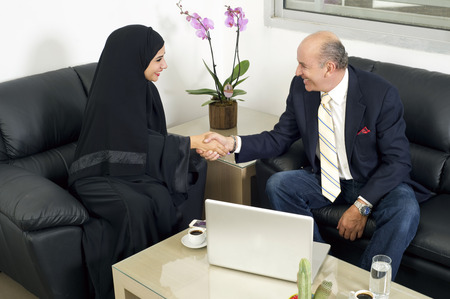 arab hijab: Senior Businessman Shaking hands with Woman wearing hijab, Multiracial Businesspeople shaking hands in office