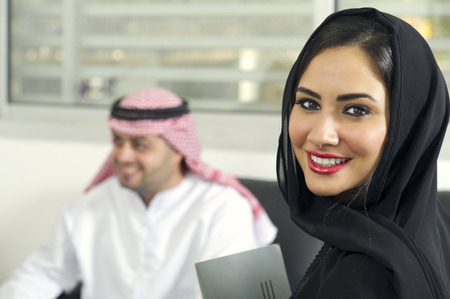 Arabian Businesswoman wearing hijab with her boss in background, Arabian businesspeople in office photo