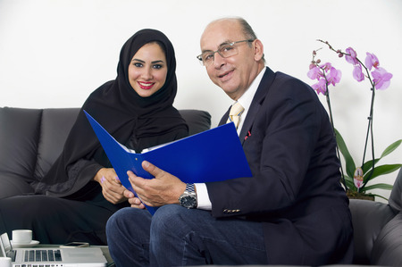 panoramic business: Senior Businessman working with arabian woman wearing hijab in office,