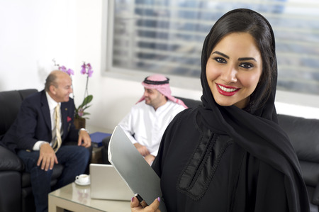 Arabian Businesswoman in office with Businesspeople meeting in the background, Arabian woman wearing Hijab in office with her colleagues in background Stock Photo
