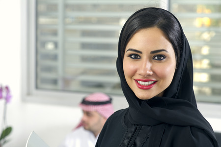 Arabian Businesswoman wearing hijab with her boss in background, Arabian businesspeople in office photo