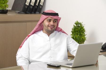 Arabian Businessman working on laptop in office photo