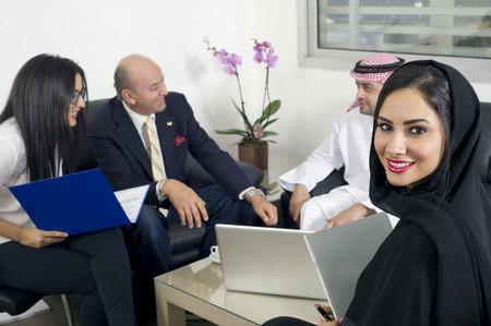 백그라운드에서 기업인 회의 사무실에서 아라비아 사업가, 배경에서 그녀의 동료와 함께 사무실에서 히잡을 착용 아라비아 여자 스톡 콘텐츠