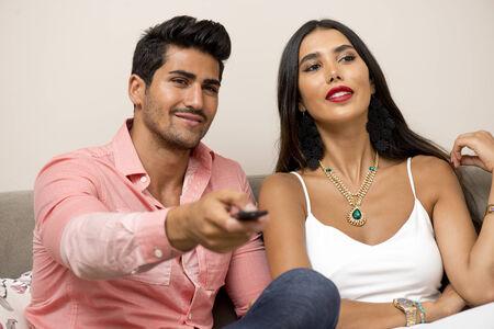 pareja viendo tv: Pareja joven de Oriente Medio viendo la televisi�n en un sof� Foto de archivo