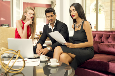 charming business lady: Portrait of a handsome fashionable man with two charming women in a business meeting Stock Photo