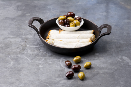 arabic food: Plate of cheese sambusek,traditional Arabic food  Cheese rolls plate with olives served in a black pan on a rustic background Stock Photo