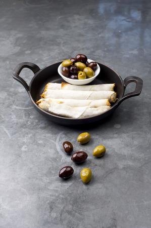 comida arabe: Plato de queso sambusek, comida tradicional �rabe  placa rollos de queso con aceitunas sirvi� en una sart�n negro sobre un fondo r�stico