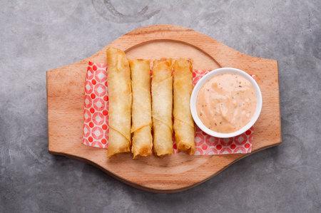 comida arabe: Plato de queso sambusek, traditiona l �rabe placa rollos comida  queso con salsa de c�ctel servido en un plato de madera sobre un fondo r�stico Foto de archivo