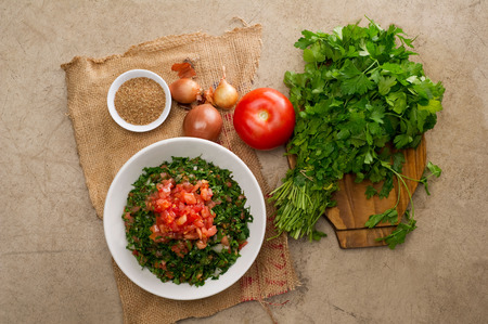 Plate of traditional Arabic salad tabbouleh on a wooden plate