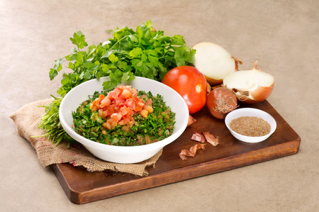 tabbouleh: Plate of traditional Arabic salad tabbouleh on a wooden plate