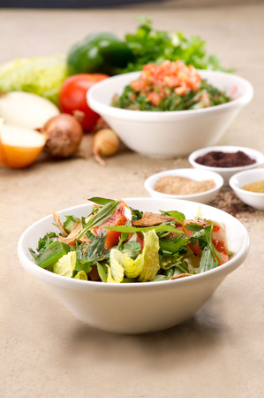 tabbouleh: Plates of traditional Arabic salad fattouch and tabbouleh on a rustic background Stock Photo