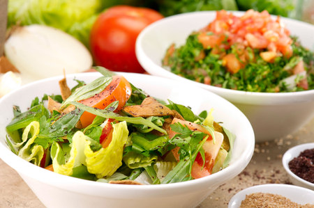 green salad: Plates of traditional Arabic salad fattouch and tabbouleh on a rustic background Stock Photo