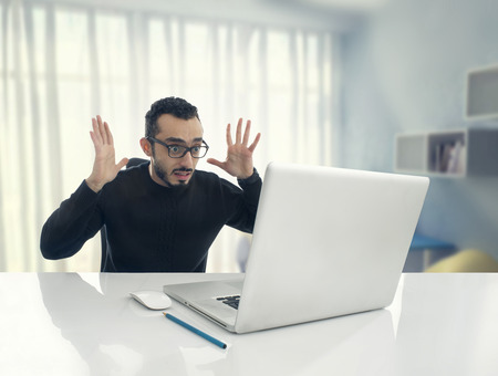 Man Shocked Reading Message on Computer in Office .
