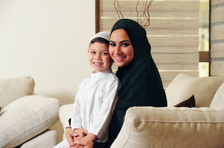 islam: Arabic family, mother and son sitting on the couch in their living room