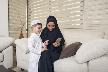 Arabian family, Arabian mother and son using mobile phone Stock Photo