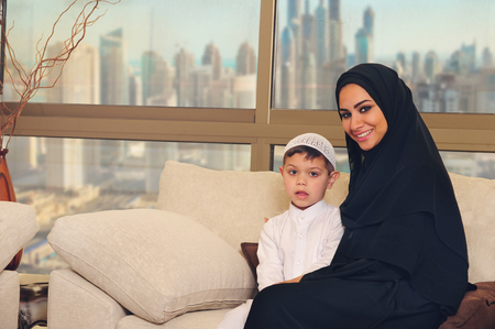 diverse family: Arabian family, mother and son sitting on the couch in their living room Stock Photo
