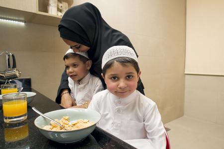 breakfast: Familia árabe de la madre y dos hijos con desayuno en la mañana