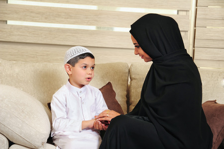 Muslim: Arabian family, mother and son sitting on the couch in their living room Stock Photo