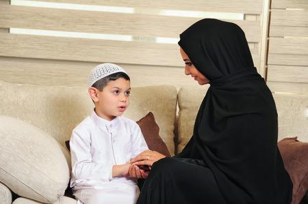familia abrazo: Familia árabe, madre e hijo sentado en el sofá de su sala de estar Foto de archivo