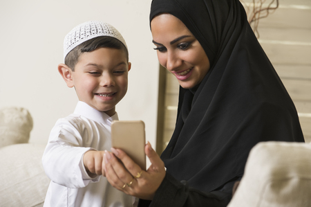 arab hijab: Arabian family, Arabian mother and son using mobile phone Stock Photo