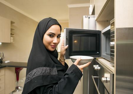 microondas: Mujer bonita joven en cocina usando microondas