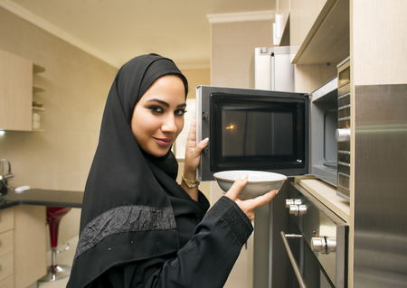 woman looking: Pretty young woman in kitchen using microwave oven Stock Photo