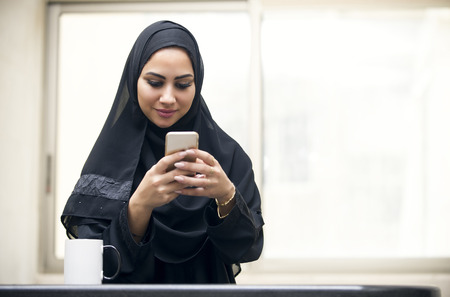 muslim: beautiful young arabian woman texting Stock Photo