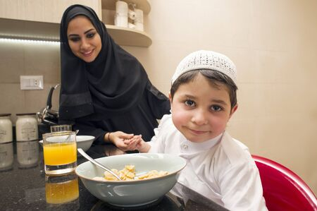 family in kitchen: Arabian family of mom and son having breakfast in the kitchen