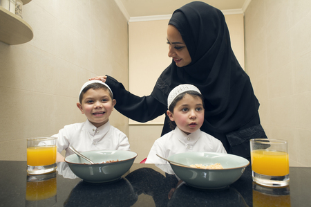 Arabian family of Mother and Two kids having Breakfast in the morning Imagens - 47352605