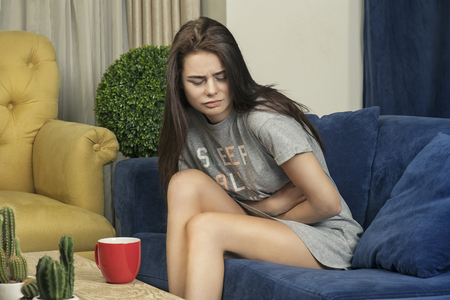 Young woman with Stomach Ache in the living room, young brunette suffering from stomach ache while sitting in a sofa
