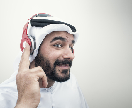 Radio: Stylish Arabian man in headphones, Arabian guy listening to music?