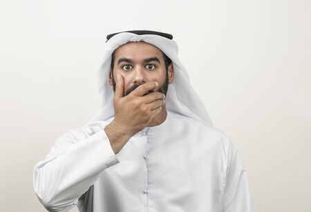 surprise face: Portrait of a shocked Arabian man covering his mouth , Arabian guy shocked